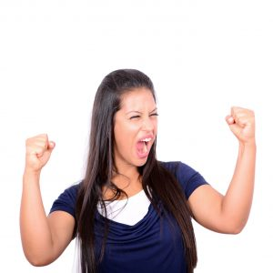 Excited happy success young woman with fists up isolated on white